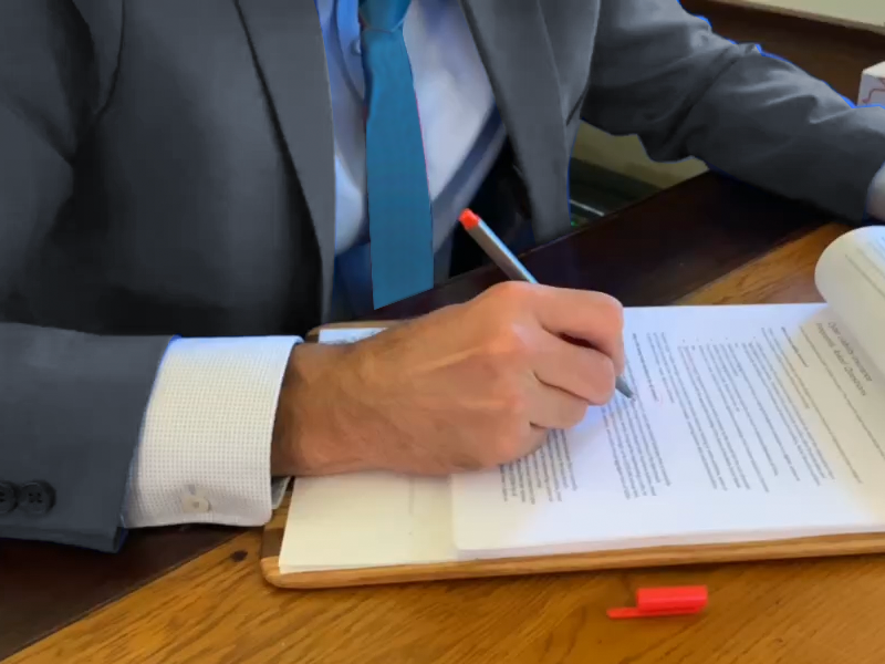 Man in gray suit signing documents